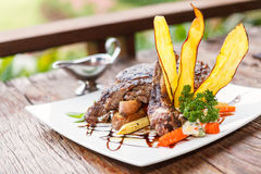 Grilled beefsteak on wooden table Royalty Free Stock Photos
