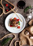 Grilled Black Angus Steak and a glass of red wine with tomatoes, rosemary royalty free stock images