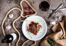 Grilled Black Angus Steak and a glass of red wine with tomatoes, rosemary royalty free stock photo