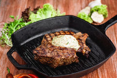 Grilled Black Angus Steak on grill iron pan on wooden black background Royalty Free Stock Photo