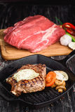 Grilled Black Angus Steak on grill iron pan on wooden black background with raw Royalty Free Stock Image