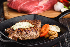 Grilled Black Angus Steak on grill iron pan on wooden black background with raw Stock Images