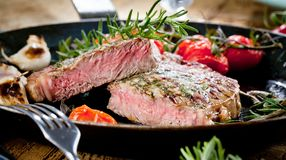 Grilled Black Angus Steak Striploin on frying cast iron Grill pan on dark background. royalty free stock photos