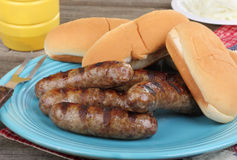 Grilled Brats. Grilled bratwursts and buns on a platter stock photography