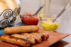 Grilled bratwurst ready to serve. Grilled brats stacked on a plate ready to serve with condiments ketchup and mustard and buns Stock Images