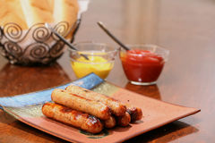 Grilled bratwurst ready to serve. Grilled brats stacked on a plate ready to serve with condiments ketchup and mustard and buns Royalty Free Stock Photo