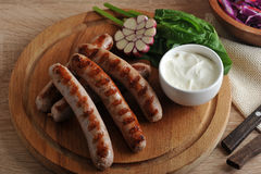 Grilled bratwurst sausages with sauce, spinach and garlic Royalty Free Stock Photo