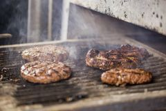 Grilled burger cutlet on hot grill with smoke. stock images