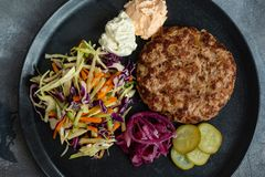 Grilled burger cutlet with onion and salad. Copy space royalty free stock photography