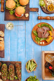 Grilled burgers, steaks, stuffed zucchini, vegetables and sauces Stock Image