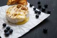 Grilled camembert cheese in paper with toasts, blueberries and walnuts on black table, closeup. Food for wine stock photos