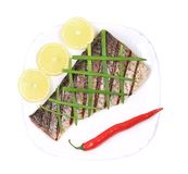 Grilled carp fillet on plate with onion and lemon Royalty Free Stock Photography