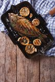 Grilled carp with lemon in a pan , vertical top view closeup. Grilled carp with lemon in a grill pan , vertical view from above closeup royalty free stock photo
