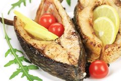 Grilled carp steaks with lemon and tomatoes. Royalty Free Stock Photos