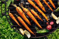 Grilled carrots in a herbal marinade on a grill plate, outdoor, top view. Grilled vegetarian food, bbq royalty free stock photos
