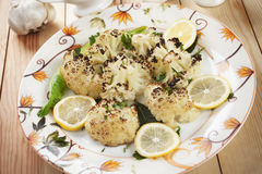 Grilled cauliflower. Served with lemon slices and herbs Stock Photos