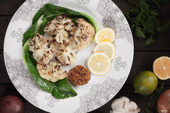 Grilled cauliflower. Served on a plate with lemon slices and mustard Royalty Free Stock Photo