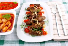 Grilled cevapcici with ajvar and giant white beans Stock Photo