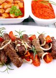 Grilled cevapcici with giant white beans and ajvar Stock Photos