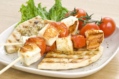 Grilled cheese(haloumi) and tomato souvlaki. A grilled souvlaki made of cyprian cheese(haloumi) and cherry tomatoes, served with greek pitta Stock Image