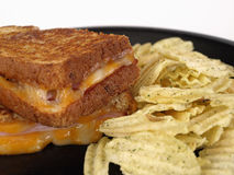 Grilled Cheese with Ham. Hot maple ham and colby jack grilled cheese sandwich. On a black plate with seasoned potato chips Stock Photography