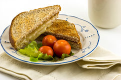 Grilled cheese sandwich. Grilled white cheddar cheese sandwich on whole wheat toast with cherry tomatoes Royalty Free Stock Image