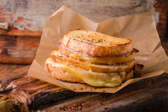 Grilled cheese sandwich with chili pepper on paper on wooden board. Selective focus. Stock Photography
