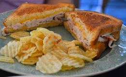Grilled cheese sandwich with turkey. And potato chips Stock Images