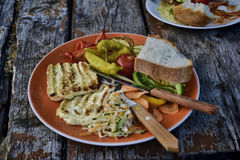 Grilled cheese with vegetables - peppers, tomato, cabbage and bread on a plate on wooden table in the garden Stock Photo