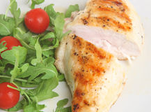 Grilled Chicken. Breast with rocket and tomato salad Stock Photos