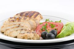 Grilled chicken. With sliced tomatoes, olives, avocado and garnished with chopped parsley artfully plated royalty free stock photo