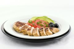Grilled chicken. With sliced tomatoes, olives, avocado and garnished with chopped parsley artfully plated royalty free stock photography