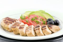 Grilled chicken. With sliced tomatoes, olives, avocado and garnished with chopped parsley artfully plated royalty free stock photos