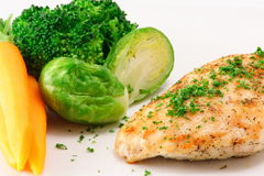 Grilled chicken. Chicken breast garnished with parsley served with steamed vegetables Stock Images