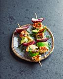 Grilled Chicken, Avocado and Red Onion Skewers with fresh herbs Stock Image
