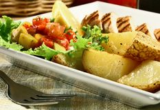 Grilled chicken breast. With mango salsa and baked potatoes royalty free stock photos
