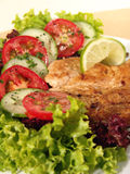 Grilled Chicken breast. Served with fresh salad, lime, tomato, cucumber, olive oil, green lettuce, and basilico royalty free stock photos