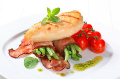 Grilled chicken breast with bacon-wrapped green beans Stock Photos