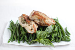 Grilled chicken breast on a bed of green beans Royalty Free Stock Images
