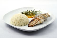 Grilled chicken breast with boiled rice. On a white plate. Raw available royalty free stock image