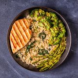 Grilled chicken breast with brown rice, spinach, broccoli, aspar stock image