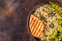 Grilled chicken breast with brown rice, spinach, broccoli, aspar royalty free stock image