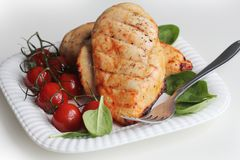 Grilled chicken breast with cherry tomatoes, spinach on a white plate Stock Image