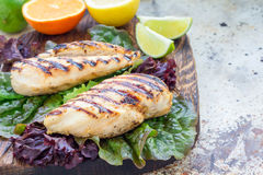 Grilled chicken breast in citrus marinade on salad leaves and wooden board, horizontal, copy space. Grilled chicken breast in citrus marinade on salad leaves and Royalty Free Stock Photography