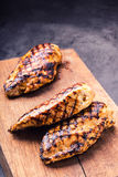Grilled chicken breast in different variations with cherry tomatoes,  mushrooms, herbs, cut lemon on a wooden board or teflon pan. Royalty Free Stock Photography