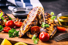 Grilled chicken breast in different variations with cherry tomatoes,  mushrooms, herbs, cut lemon on a wooden board or teflon pan. Royalty Free Stock Photos