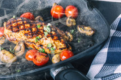 Grilled chicken breast in different variations with cherry tomatoes,  mushrooms, herbs, cut lemon on a wooden board or teflon pan. Stock Photo