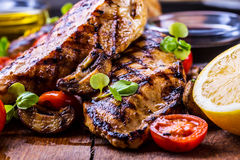 Grilled chicken breast in different variations with cherry tomatoes,  mushrooms, herbs, cut lemon on a wooden board or teflon pan. Royalty Free Stock Images