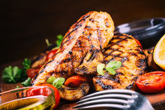 Grilled chicken breast in different variations with cherry tomatoes,  mushrooms, herbs, cut lemon on a wooden board or teflon pan. Stock Photos