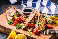 Grilled chicken breast in different variations with cherry tomatoes, mushrooms, herbs, cut lemon on a wooden board or teflon pan. Traditional cuisine. Grill royalty free stock photography